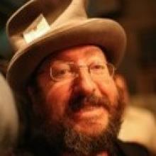 Cohousing Coach Raines Cohen, wearing a gray top hat with a card stuck in the brim.
